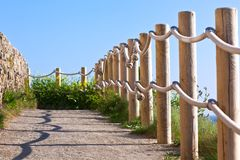 Pathway with wood post fence. Pathway with wood post and thick rope fence. Taken at Saint-Mathieu, Brittany, France Royalty Free Stock Image