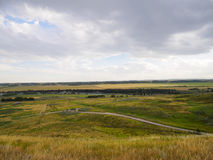 The pathways and beautiful land of Glenbow Ranch in Alberta. Looking down to the river valley of the ranch lands and the fields on a cloudy day Stock Photos