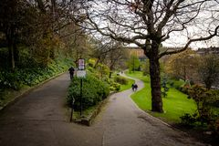 Pathways in Prince Street Gardens, with People walking along the gardens during a rainy day in spring. Edinburgh. People walking along Prince Street Gardens with royalty free stock images