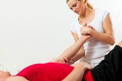 Patiënt bij de fysiotherapie die fysieke therapie doen Stock Afbeelding