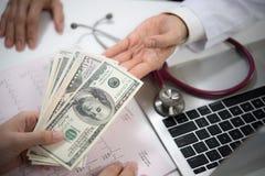 Patiënt die geld geven aan medische arts in het ziekenhuis het plaatsen stock foto's