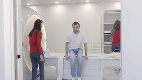 Patiënt die zich na magnetic resonance imagingsaftasten bevinden stock footage