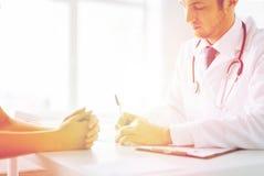 Patiënt en arts die nota's nemen Stock Foto