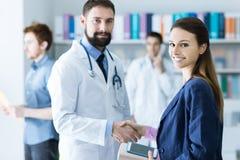 Patiënt en artsen het schudden handen stock afbeelding
