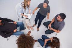 Patiënten die aan elkaar in groepszitting luisteren stock foto's