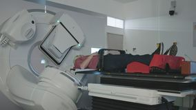 Pati?nt die de Behandeling van de Stralingstherapie binnen een moderne radiotherapieruimte krijgen stock videobeelden