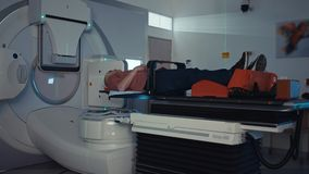 Pati?nt die de Behandeling van de Stralingstherapie binnen een moderne radiotherapieruimte krijgen stock footage