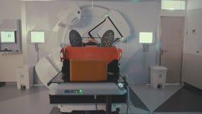 Pati?nt die de Behandeling van de Stralingstherapie binnen een moderne radiotherapieruimte krijgen stock video