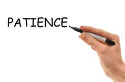Patience. White Caucasian hand writes the word Patience on the whiteboard with a marker Stock Photos