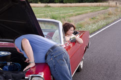 Patience. A middle-aged woman waits patiently, looking out on the rural landscape as her husband climbs under the hood of their vintage red convertible in an Stock Photos