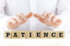 Patience. Conceptual image with the word Patience on wooden blocks or cubes protected by the hands of a man sheltering them from above Royalty Free Stock Photos