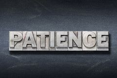 Patience word den. Patience word made from metallic letterpress on dark jeans background Stock Photos