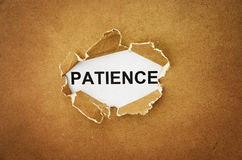 Patience. The word patience in the hole of brown paper Royalty Free Stock Photos