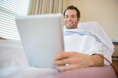 Patient à l'aide de la Tablette de Digital pendant la dialyse rénale images stock
