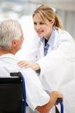 Patient aîné avec le jeune docteur féminin Photo stock