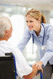 Patient aîné avec le jeune docteur féminin Image stock