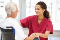 Patient aîné avec le jeune docteur féminin Image libre de droits