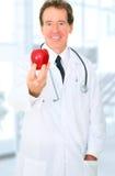 Patient aîné de docteur Offering Red Apple To Photographie stock libre de droits
