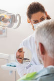 Patient admiring his new smile in the mirror Stock Photo