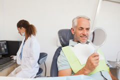 Patient admiring his new smile in the mirror Royalty Free Stock Image
