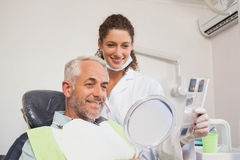 Patient admiring his new smile in the mirror Royalty Free Stock Photos