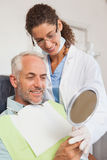 Patient admiring his new smile in the mirror Royalty Free Stock Images