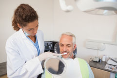 Patient admiring his new smile in the mirror Stock Images