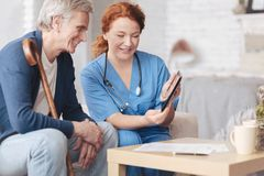 Patient amical et infirmière supérieurs regardant la tablette Photographie stock