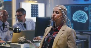 Patient answering doctors questions during brain scan. Medium shot of a female patient answering doctors questions during an EEG examination stock footage