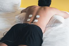 Patient applying electrical stimulation therapy on back. Electrical tens. royalty free stock photo