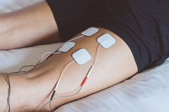 Patient applying electrical stimulation therapy on leg. Electric royalty free stock photo