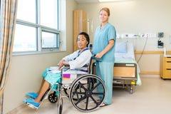Patient auf Rollstuhl während Krankenschwester Standing Behind Lizenzfreie Stockfotos