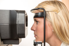 Patient and auto refractometer at optician or optometrist Royalty Free Stock Images