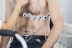 Patient avec des électrodes attachées sur le corps examiné par Docto Photos stock