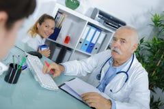 Patient ayant la consultation avec le docteur supérieur dans le bureau Photographie stock libre de droits