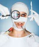 Patient in bandages and many hands holding medical instruments. Nurses holding magnifying glass, scalpel, syringe, surgical clamp near his face. Plastic Stock Image
