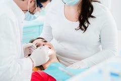 Patient behandelt vom Zahnarzt in seiner Chirurgie Stockbilder