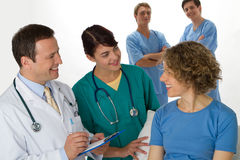 A patient being visited by a doctor and nurse Stock Photos