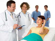 A patient being visited by a doctor and nurse Stock Photography