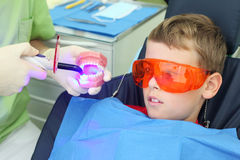 Patient boy looks at light tool Stock Photography