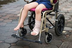 Leg broken boy sit on wheelchair. Patient boy sitting on wheelchair to give a walk and refreshment in park. Closeup Broken leg by accident wrapped with plaster royalty free stock images