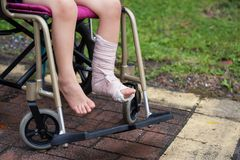 Leg broken child sit on wheelchair. Patient boy sitting on wheelchair to give a walk and refreshment in park. Closeup Broken leg by accident wrapped with plaster royalty free stock images