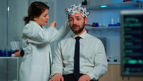 Patient with brainwave scanning headset sitting in brain study lab