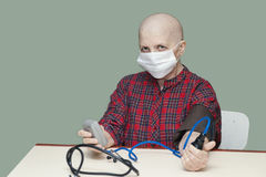 Patient breast cancer bald woman controls your blood pressure in a sterile mask Royalty Free Stock Photo