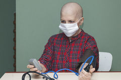 Patient breast cancer bald woman controls your blood pressure in a sterile mask Stock Photos