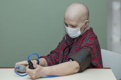 Patient breast cancer bald woman controls your blood pressure in a sterile mask Royalty Free Stock Photography