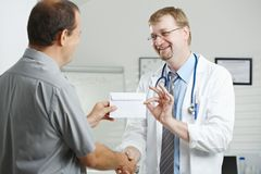 Patient bribing doctor Stock Photography