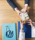 Patient bribing a greedy doctor Stock Photos