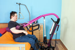 Patient with cerebral palsy using a patient lift. Royalty Free Stock Images