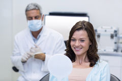 Patient checking her teeth in mirror Stock Image